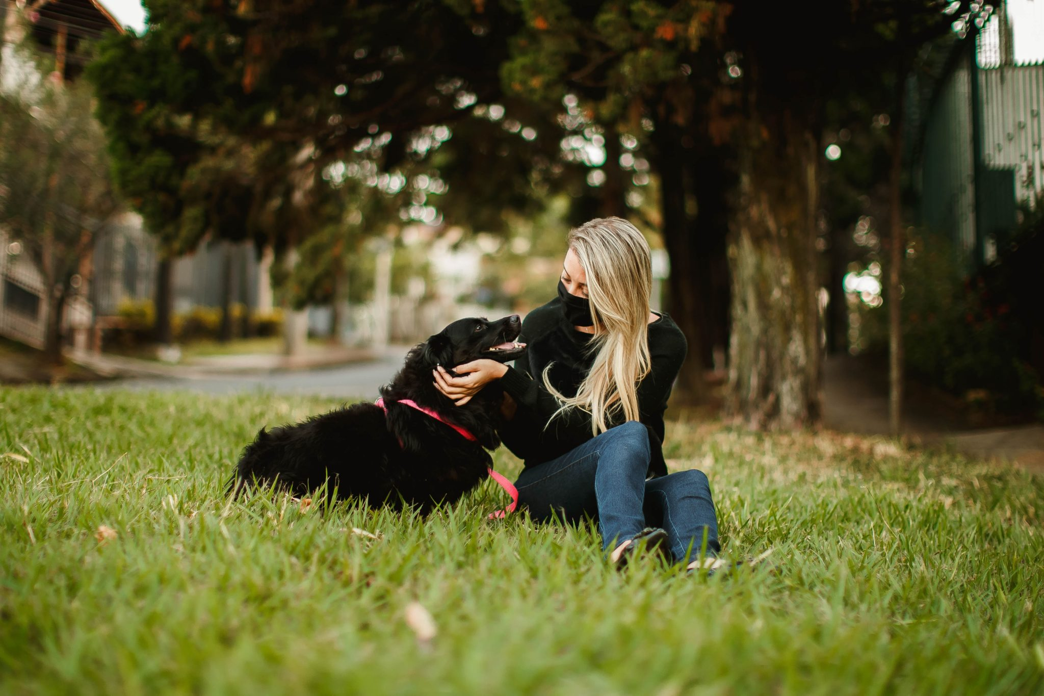 Masked woman playing with puppy in park