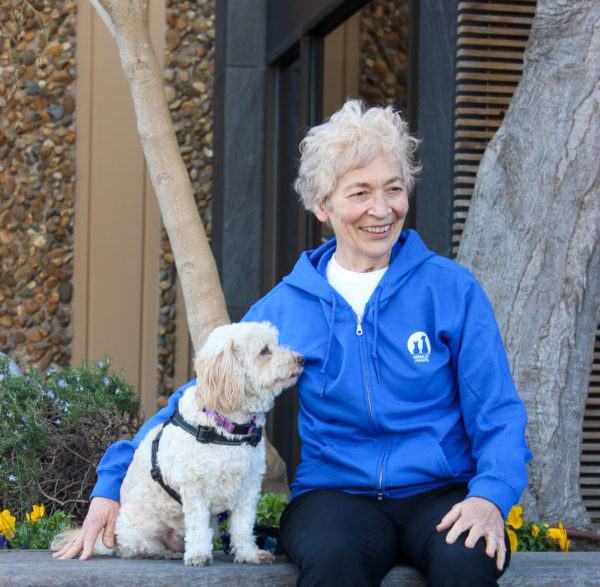 image of women wearing blue hoodie sitting next to fluffy dog