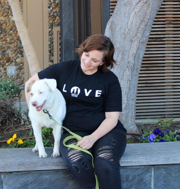 image of women wearing black love t-shirt sitting next to dog