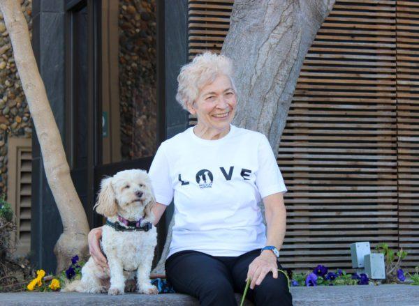 image of women wearing white love t-shirt sitting next to fluffy dog