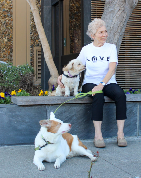 image of women wearing white love t-shirt sitting next to two dogs